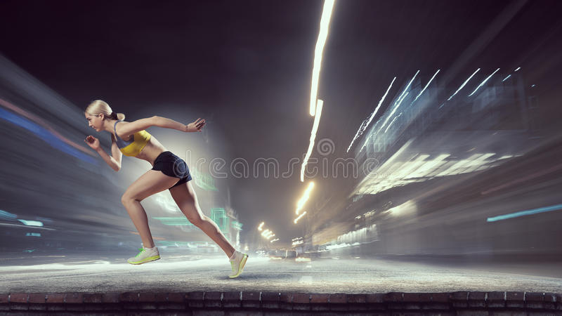 Your best motivation. Mixed media. Young woman athlete running fast on dark background. Mixed media royalty free stock image