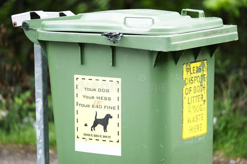 Your dog mess fine notice and please dispose of litter and waste sign on green wheelie bin stock image