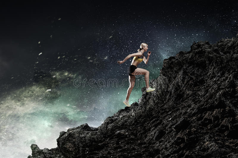 Your endless energy. Slim attractive sportswoman running up the hill. Mixed media stock image