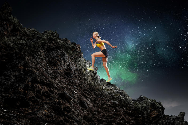 Your endless energy. Slim attractive sportswoman running up the hill. Mixed media stock images