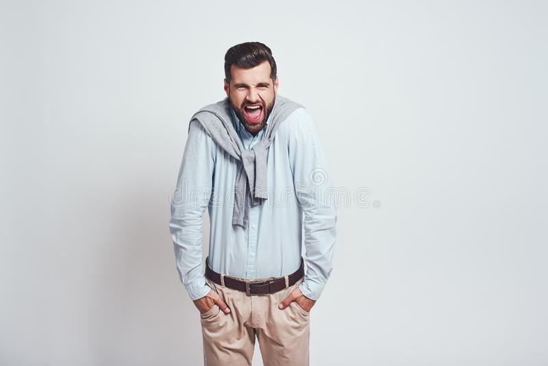 It is your fault. Angry young man is looking at camera and shouting, keeping hands in his pockets while standing against royalty free stock photo