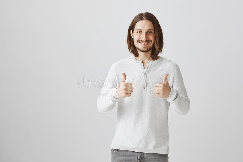 Your idea is super, like it. Studio portrait of creative handsome guy with beard showing thumbs up and smiling royalty free stock image