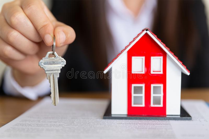 Your new house, real estate agent holding house key to his client after signing contract agreement in office,concept for real stock photos