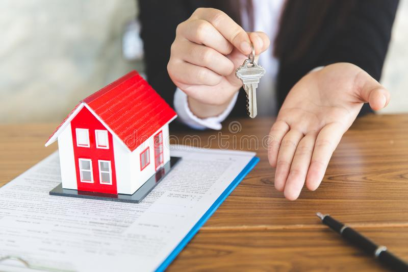Your new house, real estate agent holding house key to his client after signing contract agreement in office,concept for real royalty free stock photos