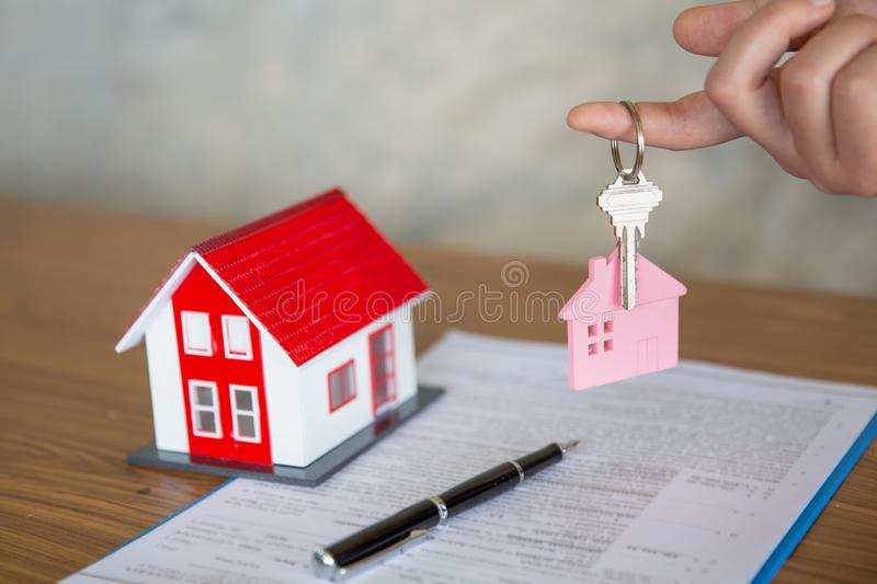 Your new house, real estate agent holding house key to his client after signing contract agreement in office,concept for real royalty free stock photography