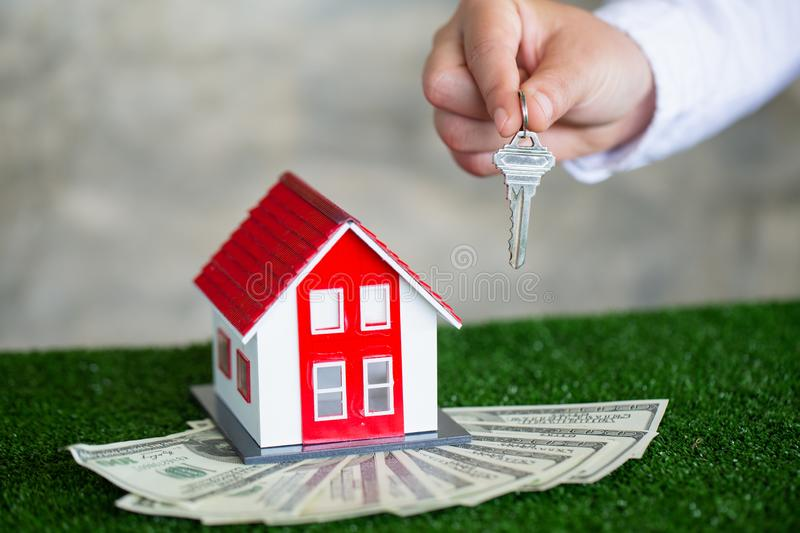 Your new house, real estate agent holding house key to his client after signing contract agreement in office,concept for real royalty free stock images