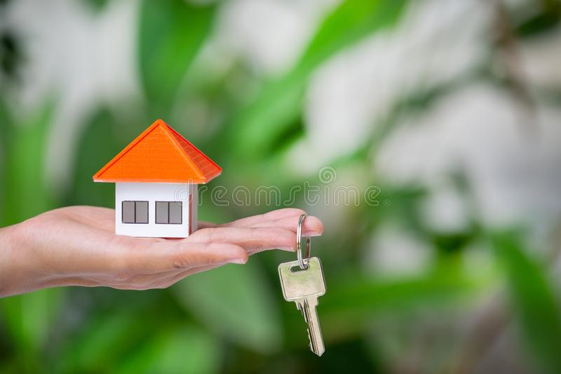 Your new house, woman hands holding a  model house and key. Mortgage property insurance dream moving home and real estate concept stock photo