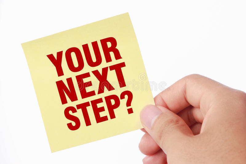 Your Next Step. Hand with Your Next Step note is isolated on white background royalty free stock image