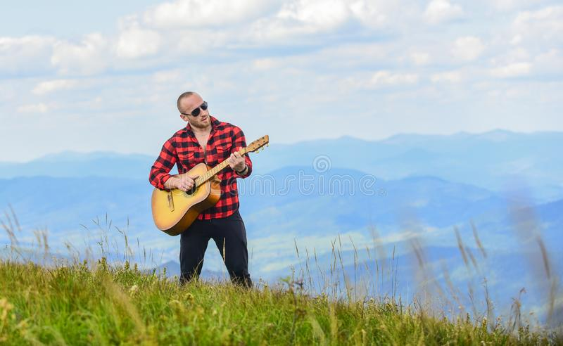 Your number one rock station. acoustic guitar player. country music song. sexy man with guitar. hipster fashion. western. Camping and hiking. happy and free royalty free stock photos