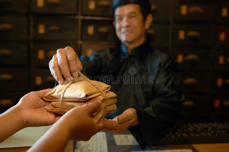 This is your order. Traditional Chinese medicine practitioner giving packs with herbs to the customer royalty free stock photos