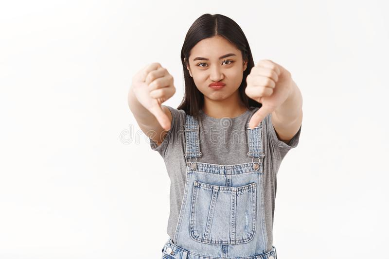 Your party for losers sucks. Displeased moody ignorant asian brunette girl express disapproval dislike frowning sulking. Upset show thumbs down rate awful stock photo