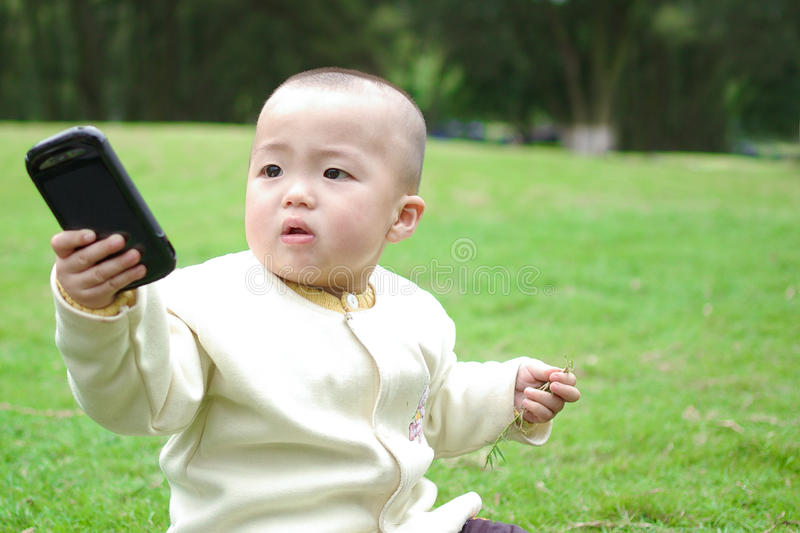 Your phone. A child sitting on the grass holding a phone royalty free stock photos