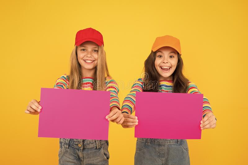 For your product. Happy children holding empty sheets of paper. Little children smiling with pink drawing paper. Small. Children with blank advertisement poster stock photography