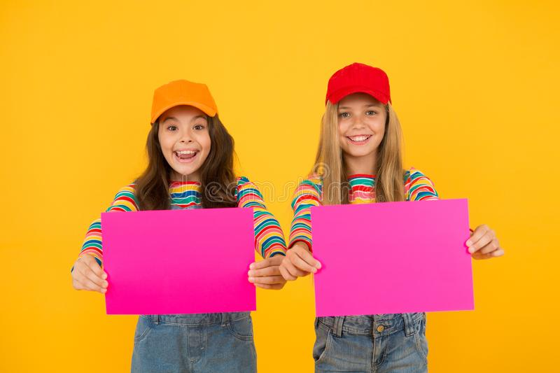 For your product. Happy children holding empty sheets of paper. Little children smiling with pink drawing paper. Small. Children with blank advertisement poster royalty free stock photography