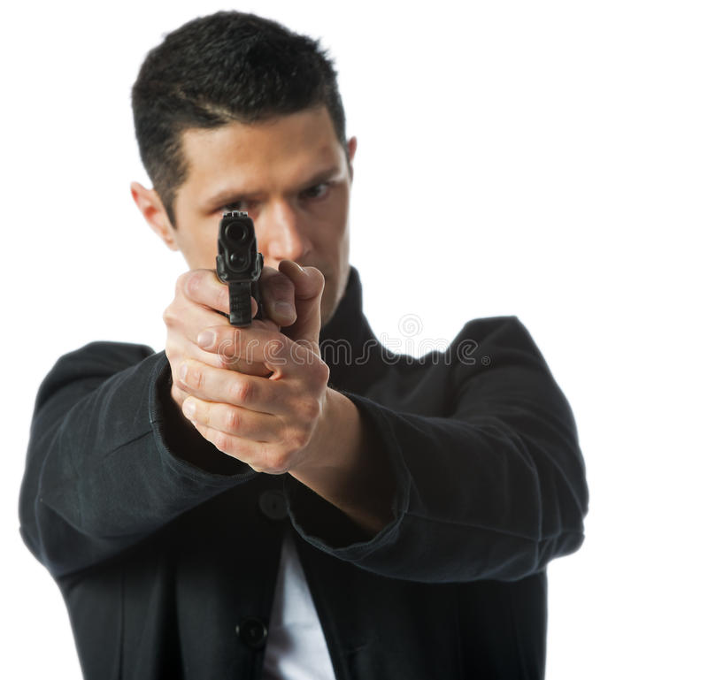 In your sights. Isolated on a white background a young man lines up his sights on the pistol ready to fire at his target royalty free stock photos
