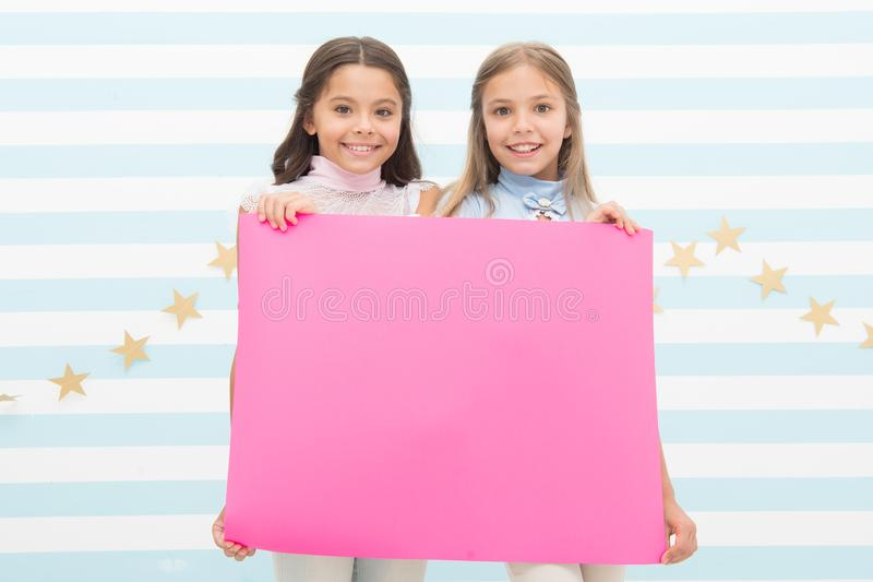 For your text. Happy children holding empty sheet of paper. Little children smiling with pink drawing paper. Small. Children with blank advertisement poster stock photo