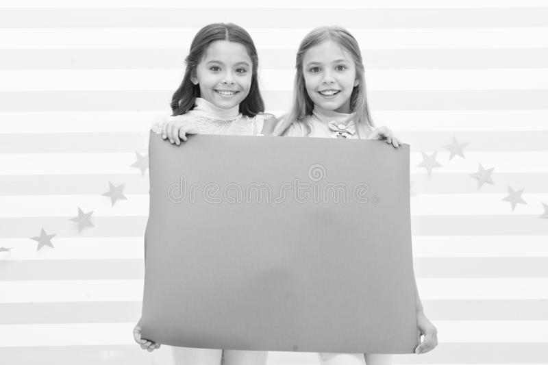 For your text. Happy children holding empty sheet of paper. Little children smiling with pink drawing paper. Small. Children with blank advertisement poster royalty free stock photography