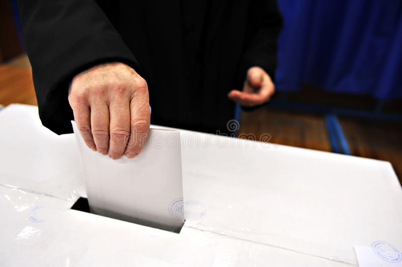 Your vote counts. Close-up of a man's hand putting his vote in the ballot box stock images