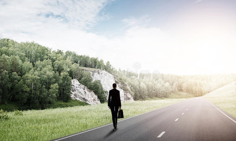 Your way to success. Elegant businesswoman on road standing with back and looking ahead royalty free stock photos