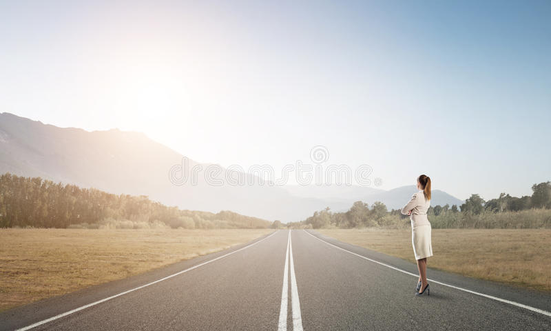 Your way to success. Elegant businesswoman on road standing with back and looking ahead stock photo