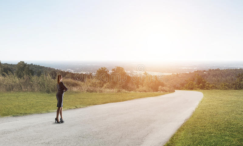 Your way to success. Elegant businesswoman on road standing with back and looking ahead royalty free stock image