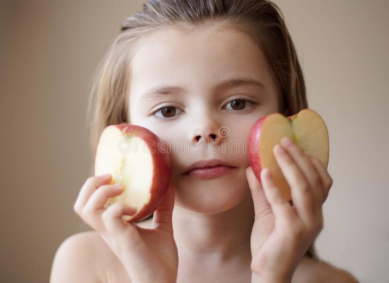 Your whole body will be grateful. Little girl holding apple. Close up stock photo