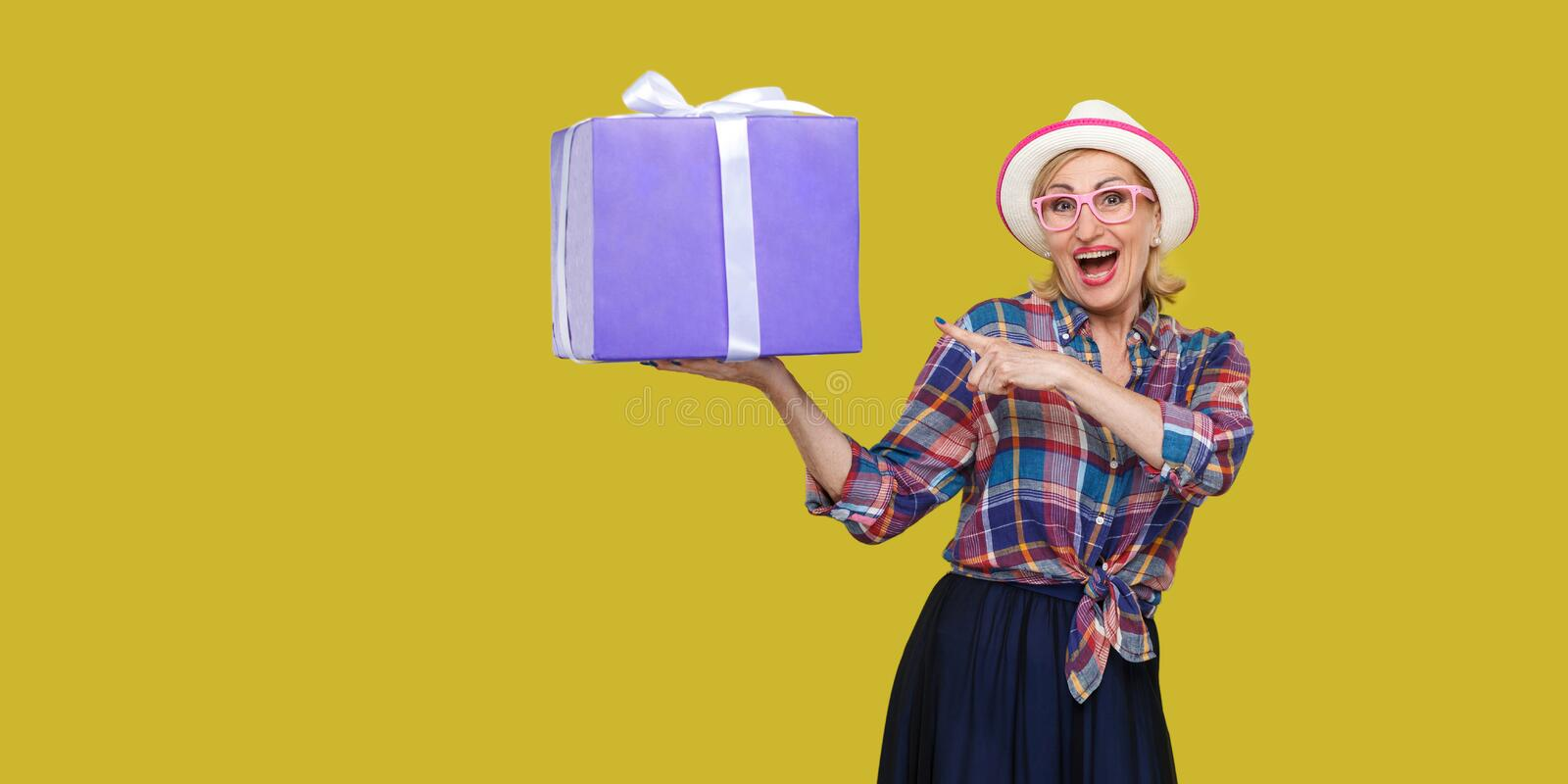 It is yours? Happy beautiful modern grandma in white hat and in checkered shirt standing, surprised holding big gift box with. Pointing finger to it, looking at stock image