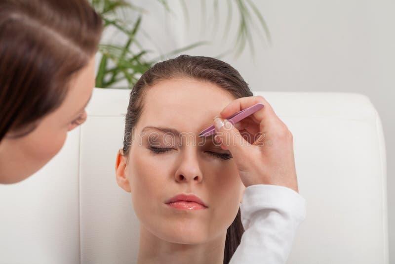 Youtg beautiful woman eyebrow plucking tweezers eyes hair. Youtg beautiful women eyebrow plucking tweezers eyes hair closeup portrait stock images