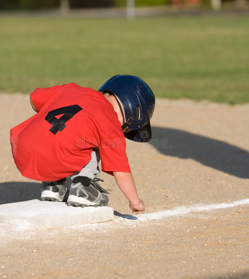 Youth baseball player. Picking up dirt while on first base stock photos