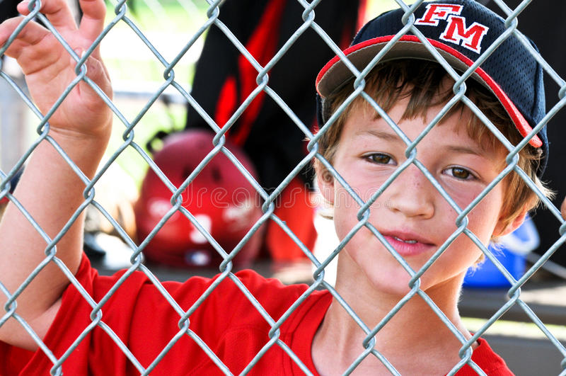 Youth baseball player in dugout royalty free stock image