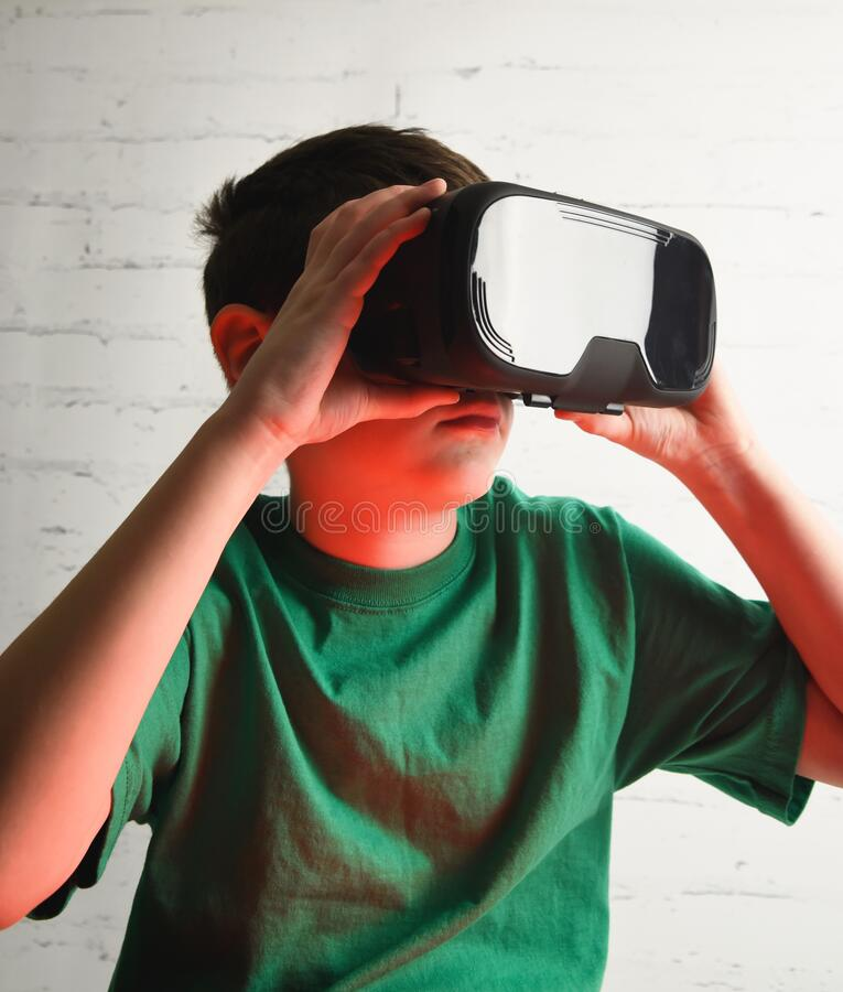 Boy Using Technology VR Goggles in Room stock images