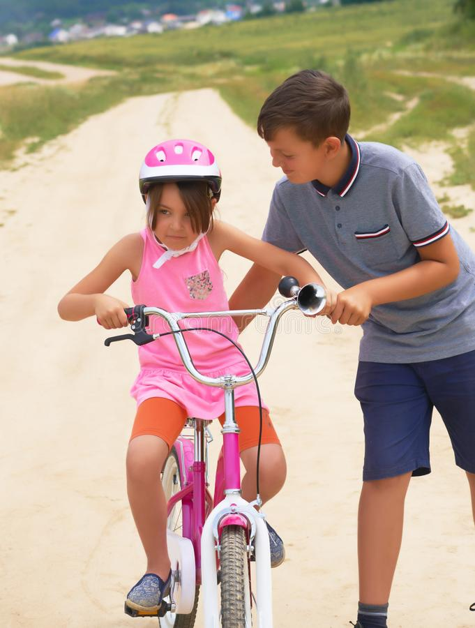 Youth brother teaching his younger sister to ride a bike. Little girl in a pink protective helmet on a pink bike rides stock images