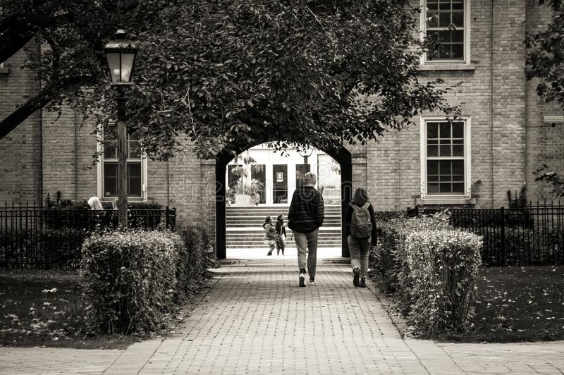 A youth couple walking along the park alley in front of old building towards the arch exit to the street.  stock photos