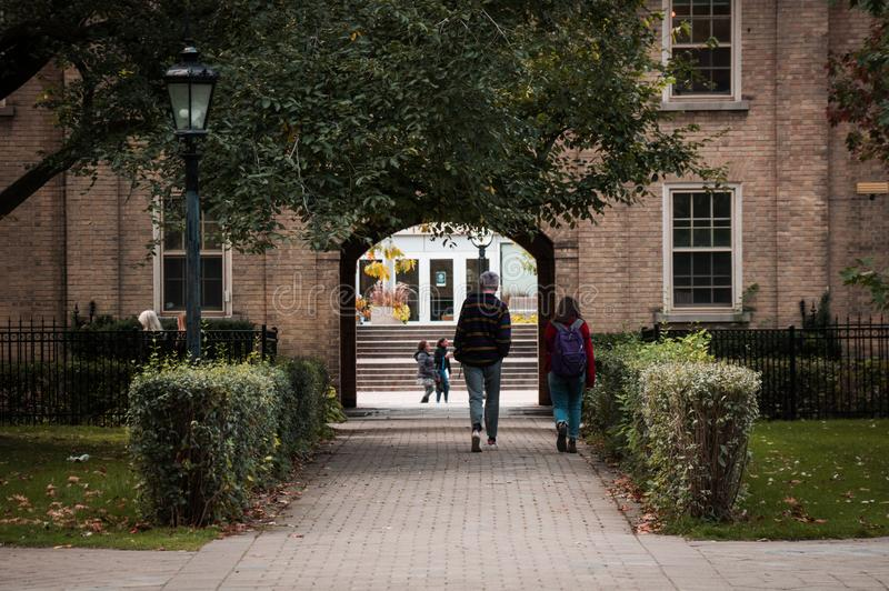 A youth couple walking along the park alley in front of old building towards the arch exit to the street.  stock images