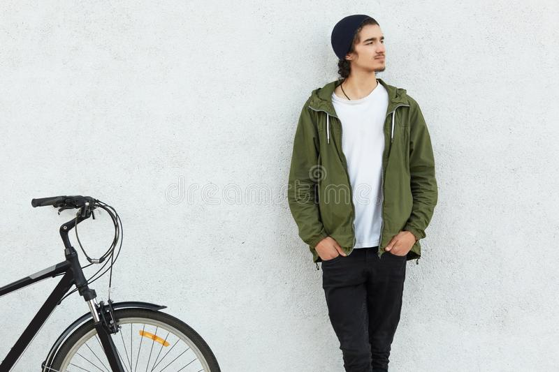 Youth and cycling concept. Stylish guy dressed in hat, green jacket, keeps hands in pocket, stands near sport bicycle, focused asi stock photography