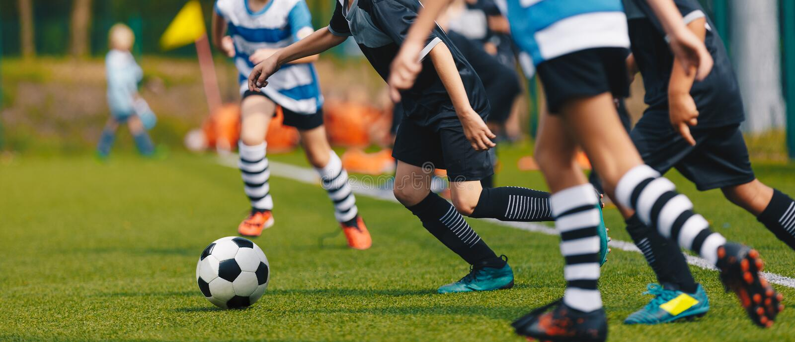 Youth Footballers Running on Grass Football Pitch and Kicking Ball royalty free stock image