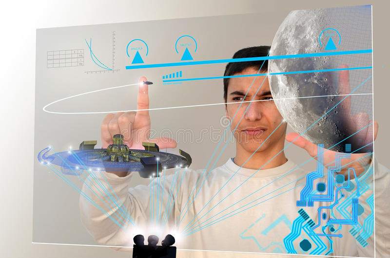 Youth for the future. A young boy faces a transparent modern computer screen, working on orbital calculations of futuristic spaceships and spatial station. A royalty free stock photos