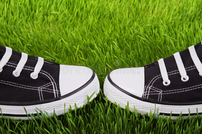 Youth gym shoes on a green grass. Couple youth sneakers, black and white sneakers, shoes on the green grass, outing, footwear close-up, green lawn, shoes for stock image