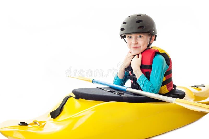 Youth Kayaker. Youth kayak paddler portrait in the studio, sitting in his kayak royalty free stock photo