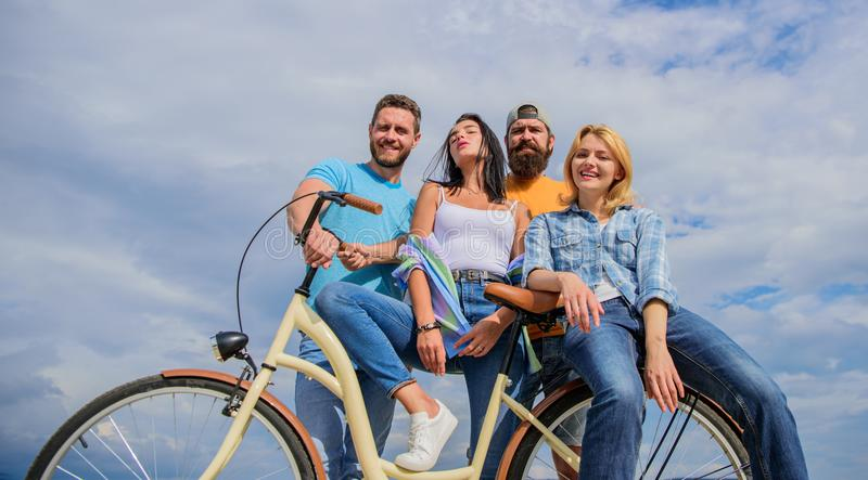 Youth likes cruiser bike. Cycling modernity and national culture. Company stylish young people spend leisure outdoors. Sky background. Group friends hang out stock photography