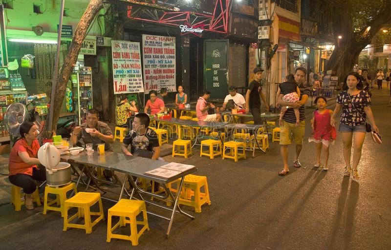 Youth people are eating at street food vendors in Hanoi`s stock photo