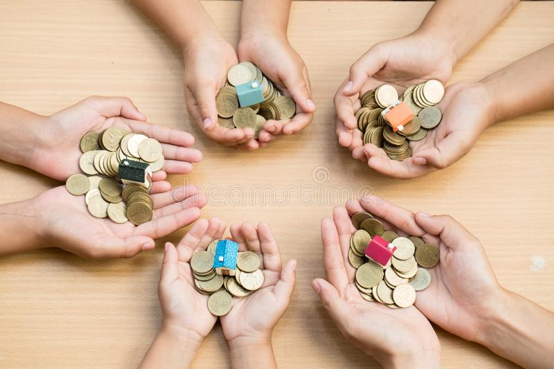 Youth show hand holding a model home and coin and the wooden background, Saving money for buy a new house and loan for plan royalty free stock photo