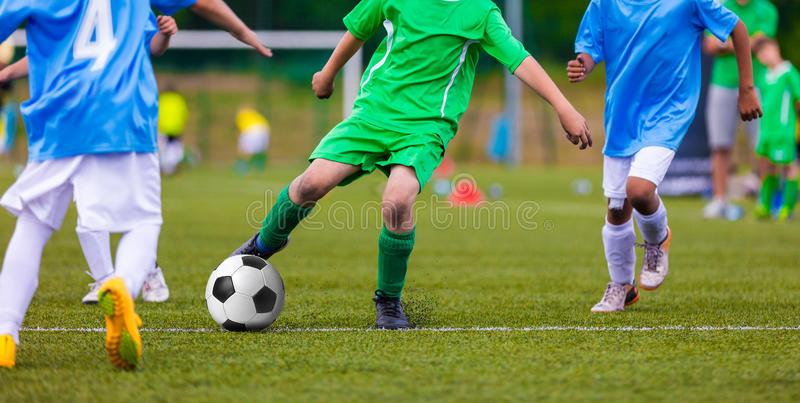Youth soccer football teams kicking soccer ball on sports field. Youth soccer football teams kicking soccer ball on a sports pitch. Soccer tournament for young royalty free stock photos