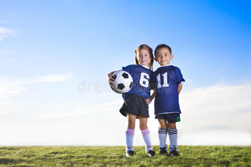 Youth Soccer Players. Two cute youth soccer players wearing their team uniforms. Boy and girl of hispanic ethnicity. Lots of copy space stock photo