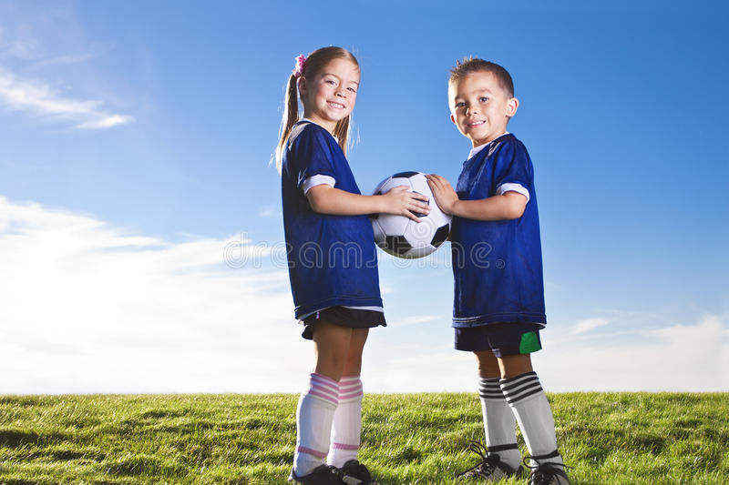 Youth Soccer Players. Two cute youth soccer players wearing their team uniforms. Boy and girl of hispanic ethnicity. Lots of copy space stock image
