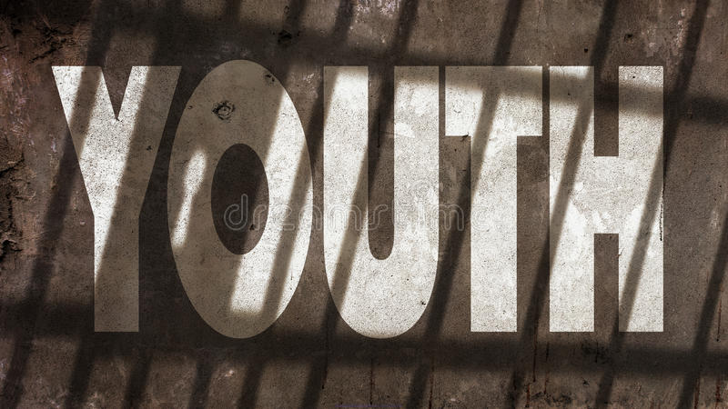 Youth On A Wall With Jail Bars Shadow. Youth Written On A Wall With Jail Bars Shadow stock photos