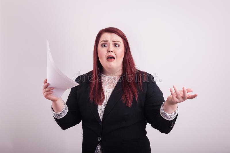 Youthful business woman in black suit stressed expression stack of papers in one hand other arm raised. Youthful red haired business woman in black suit holding stock images