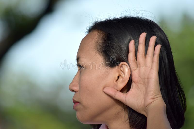 Youthful Diverse Female Hearing. An attractive and asian person stock photography