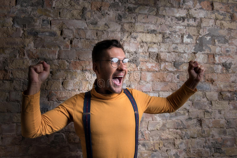 Youthful exited male standing against brick wall stock photo
