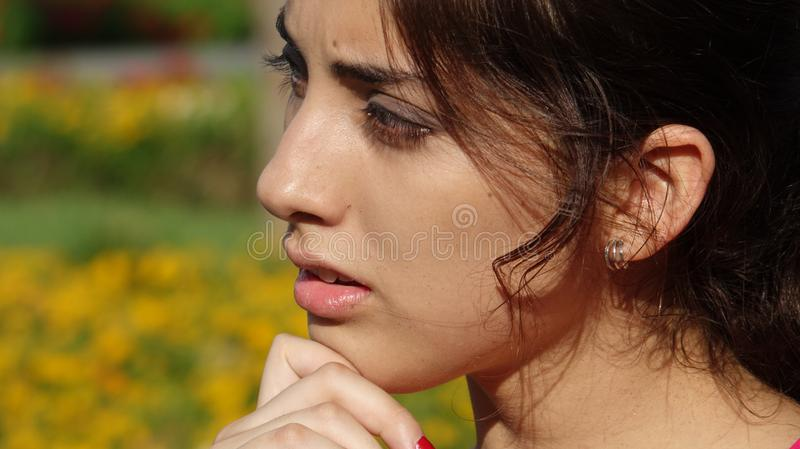 Youthful Female Making A Decision. A pretty young Peruvian adult female stock image